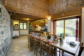 Cuisine équipée et salle à manger avec une grande table pour 10-12 personnes.
