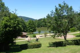 Chalet-Gîte du Plan d'eau d'Azole (Gîte N° 4) à Propières (Rhône - Beaujolais Vert)  : espaces verts avec aire de jeux et vue sur le plan d'eau.