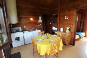 Chalet-Gîte du Plan d'eau d'Azole (Gîte N° 6) à Propières (Rhône - Beaujolais Vert) : séjour, espaces repas et cuisine.