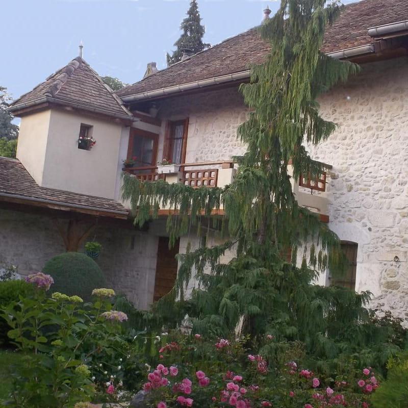 Le gîte vu du patio en fleurs , le toit a retrouvé ses petites tuiles  et  la façade ses pierres apparentes d'origine.
