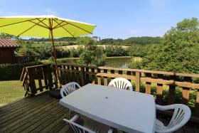Chalet-Gîte du Plan d'eau d'Azole (Gîte N° 6) à Propières (Rhône - Beaujolais Vert) : la terrasse avec vue sur le plan d'eau.