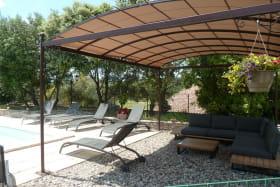 Salon de jardin et pergola au bord de la piscine