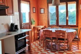 Le coin repas de la cuisine avec vue sur la montagne et l'accès à la terrasse