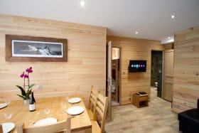 Espace cuisine ouvert sur le salon salle à manger, avec accès direct au jardin et terrasse avec salon de jardin et barbecue
