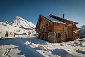 Le chalet avec à l'étage sur deux niveaux le gîte, au RDC le Thé Lait Ski (salon de thé, crêperie), sur la gauche les pistes de ski, le départ des cours ESF et en arrière plan le Mont Emy