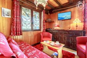 Espace salon avec banquette, 2 fauteuils, table basse et télévision murale