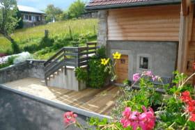 Cour, escalier d'accès au gîte, terrasse et porte de la salle de jeux. Accès à la buanderie (machine à laver, sèche-linge, local à skis, vélos)