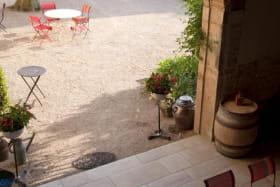 Le chemin vous amène au préau, lieu de vie semi ouvert sur le jardin