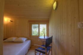 Une chambre avec un espace lecture au besoin et une très belle vue sur la nature.