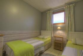 Chambre composée de deux lits simple avec une jolie vue sur la campagne environnante.