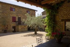 Gîte - 36 personnes - Le « Relais des pierres Dorées » à Lacenas dans le Beaujolais - Rhône : Terrasse couverte avec vue sur la cour fermée.