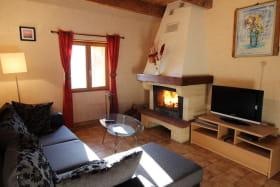 Le salon du gîte avec le canapé d'angle, la cheminée insert agréable ( le bois est fourni ) et la TV.