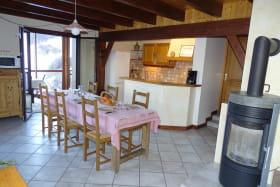 L'espace repas et la cuisine avec accès à la véranda