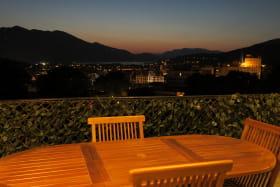vue sur la ville et le lac, table repas, coin salon, transat, parasol