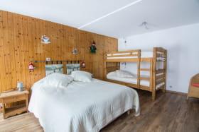 Grande chambre avec un lit pour deux personnes et deux lits superposés