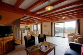 Grande pièce à vivre lumineuse de 43 m² avec 2 baies vitrées offrant une belle vue sur la nature.