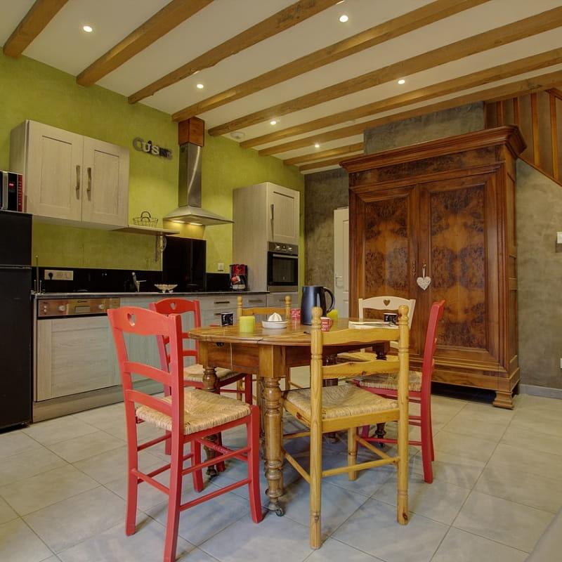 Cuisine équipée et ouverte sur la pièce de vie. Le bois s'intègre dans cette décoration épurée et chaleureuse.
