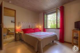 Chambre composée d'un lit en 140 avec vue sur l'espace extérieur.
