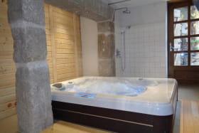 Espace bien-être avec spa, hammam, douche et WC.