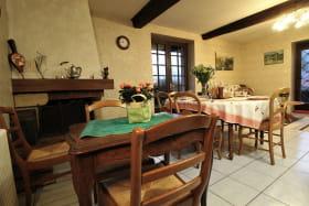 'Gîte du Bistinclin Fruité' à Saint Laurent d'Agny (Rhône, Ouest Lyonnais, proximité Brignais / Mornant) : pièce de jour avec table pour jeux et cheminée décorative.