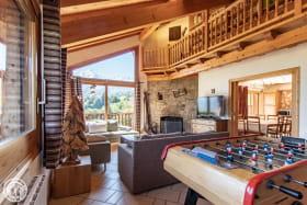 Salon et cheminée en pierres sèches. 2 canapés 3p et 2 fauteuils. Baby foot. Face au Mont-Blanc et aux Fiz.