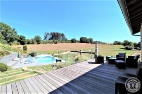 Grand gîte des Chambres de L'Ouest à Longessaigne (Rhône, Monts du Lyonnais) : grande terrasse en bois (60 m²) avec vue sur piscine.