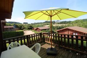 Chalet-Gîte du Plan d'eau d'Azole (Gîte N° 3) à Propières (Rhône - Beaujolais Vert) : la terrasse avec parasol.