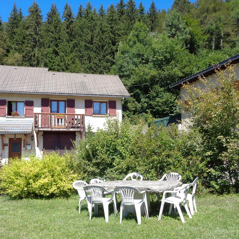 Gîte avec balcon, petit jardin privatif & salon de jardin à l'arrière plan. Jardin & aire de jeu en commun au 1er plan.