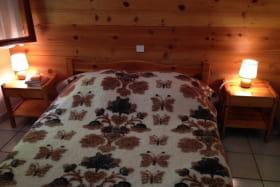chambre n°1 lit double 2 tables de nuit 1 armoire : penderie + étagères