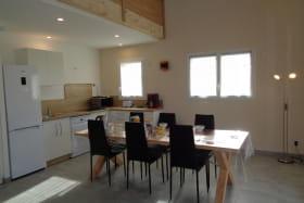 Séjour avec cuisine ouverte sur l'espace repas et le salon.