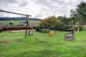 terrain de jeux ombragé: balançoire,trampoline,toboggan, bain de soleil,jeux de boules.