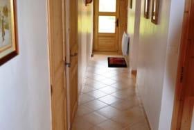 Couloir desservant toutes les pièces avec au fond l'entrée principale.