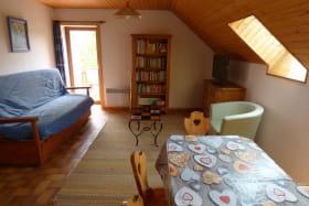 Séjour ouvert sur la terrasse, avec son coin TV/bibliothèque.