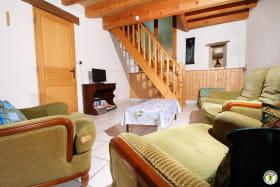 Salon vu de la Salle à manger. Au fond, escalier menant aux chambres. A gauche, porte desservant un SAS donnant accès à la salle de bain et aux toilettes séparées.